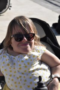Girl with short stature in power chair smiling wiith sunglasses