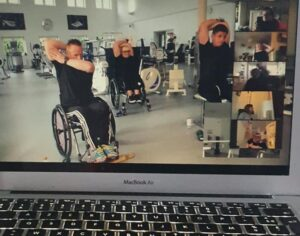 Photo of a Mac showing a video of people in wheelchairs doing cardio exercise