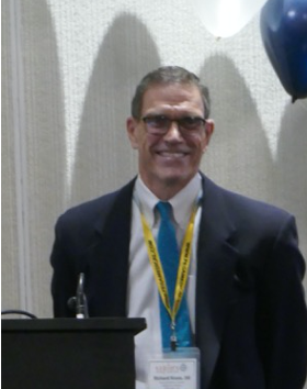 Photo of OI-expert Richard Kruse wearing a suit and a conference badge.