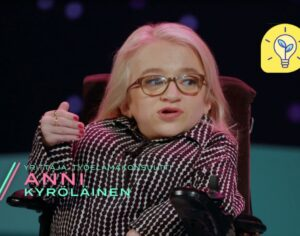 Small blonde woman with OI sitting in a TV-studio explaining something.