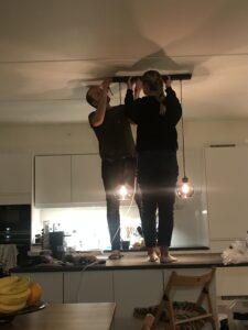 Man and woman standing on kitchen counter mounting a lamp