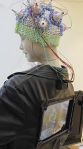 Doll with cap of electroencephalogram and tablet on its back